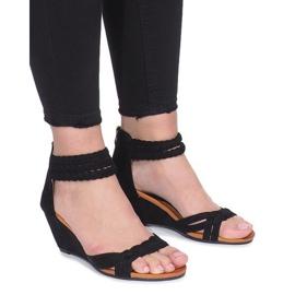 Sorte sandaler på en delikat Desun-kile